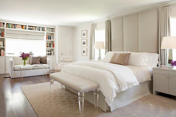 White and gray bedroom features a tall gray padded headboard, which touches  the ceiling, flanked by gray nightstands and mirrored lamps placed under  windows ...