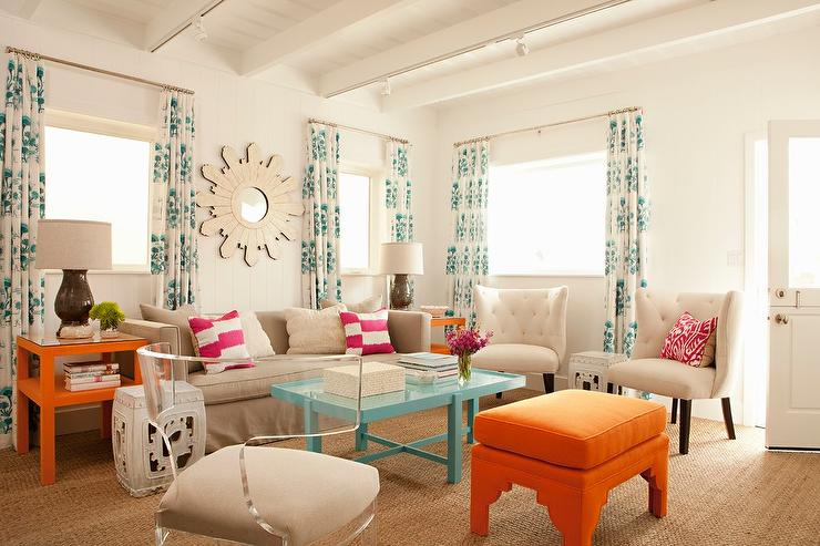 Lovely Living Room Features A Wood Sunburst Mirror Placed Above Gray Sofa Lined With Hot Pink Striped Pillows Flanked By Orange End Tables Under