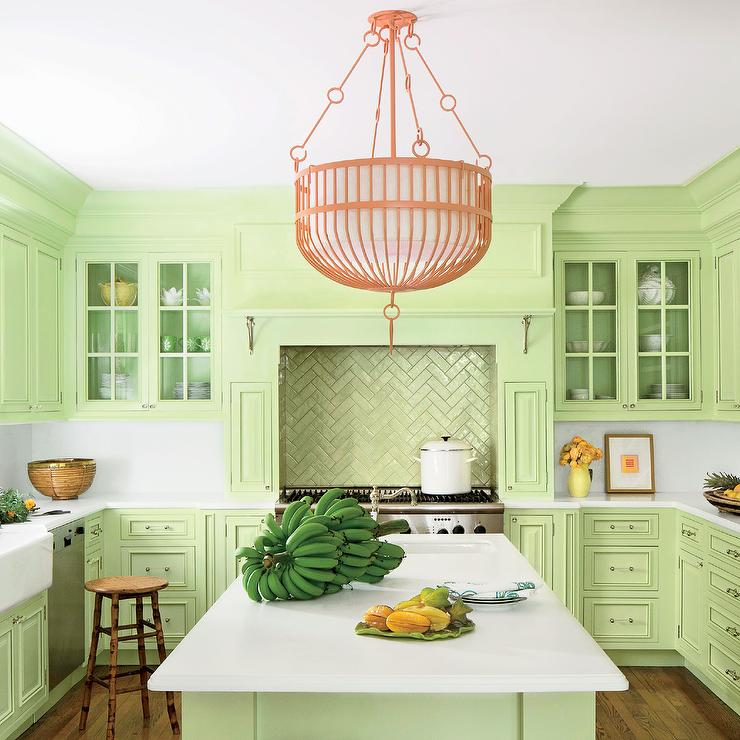A coral pink chandelier hangs over a light green island topped with white  Corian countertops fitted with a sink and a polished nickel hook and spout  faucet.