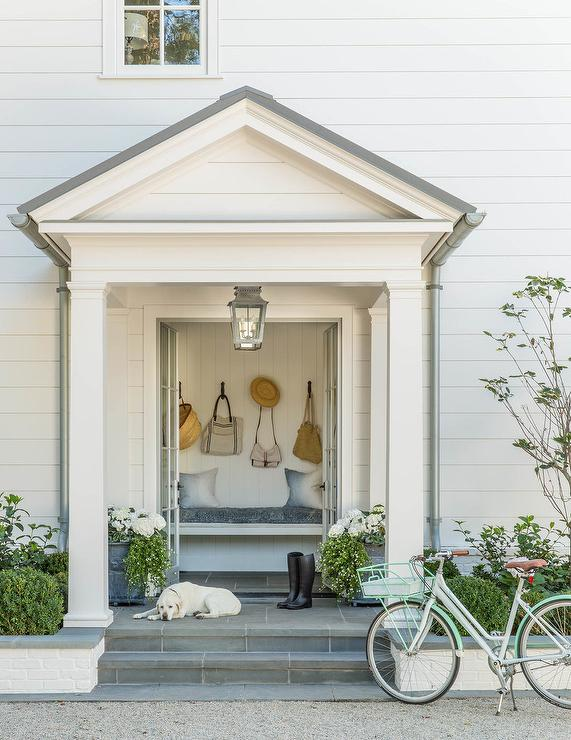 Cottage home features a steps up to a portico filled with French doors opening to reveal a long built-in bench. : portico door - pezcame.com