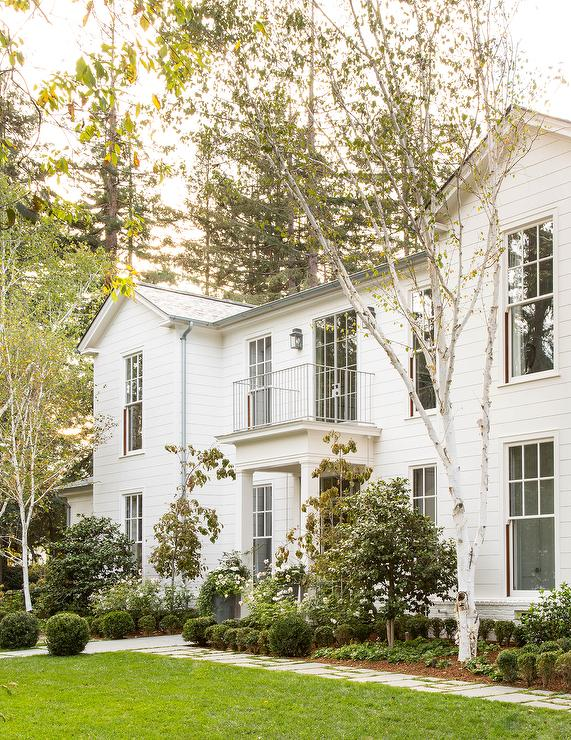 Traditional home exterior boasts a small balcony over a portico. White home  exterior is accented with white paneling as well as white brick.