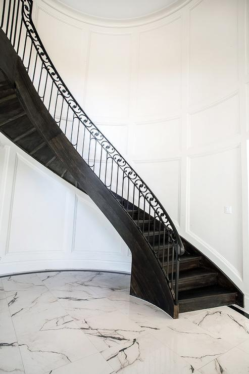 Dark Stained Wood Curved Staircase With Ornate Banister
