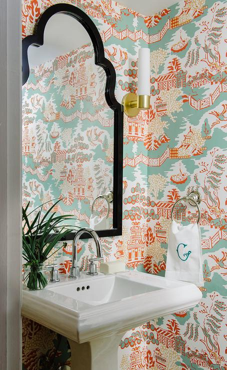 Clad in thibaut luzon wallpaper this charming blue and orange powder room is equipped with a black arched mirror mounted above a pedestal sink finished