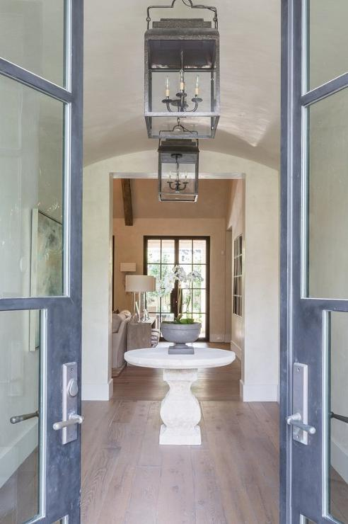 Glass Double Doors Open To A Foyer Featuring A Round Stone Pedestal Table  Placed In The Center Of The Room Illuminated By A Vintage Lantern.