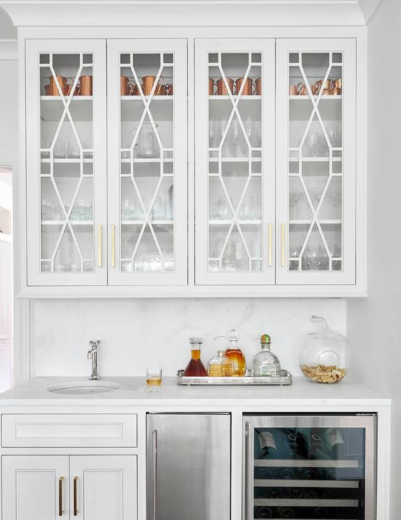 chic wet bar features white cabinets topped with white marble fitted with a round sink and a polished nickel faucet placed next to a stainless steel mini
