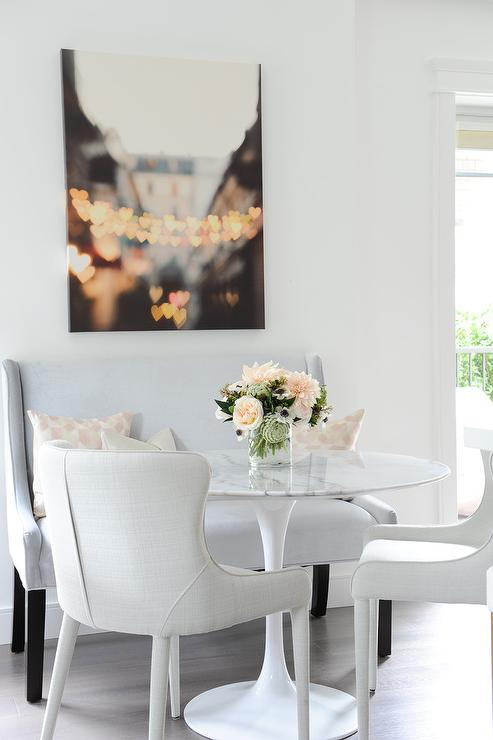 Romantic Dining Area Features A Saarinen Table Seating Two White Linen Chairs And Light Gray Wingback Settee Positioned Under Hearts Over