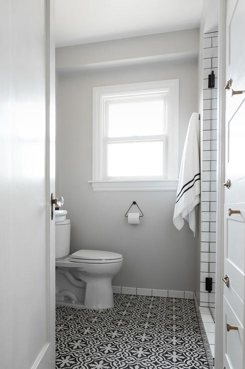 white and gray bathroom with black and white cement floor tiles