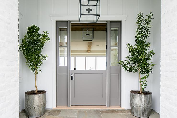 a gray dutch front door flanked by sidelights is framed by a white paneled home exterior illuminated by an iron and glass cube lantern hung between two
