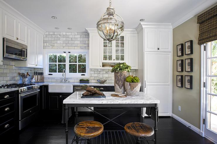 Charming L Shaped Kitchen Features White Upper Cabinets And Black Lower Cabinets  Paired With Marble Countertops And A Marble Subway Tiled Backsplash.