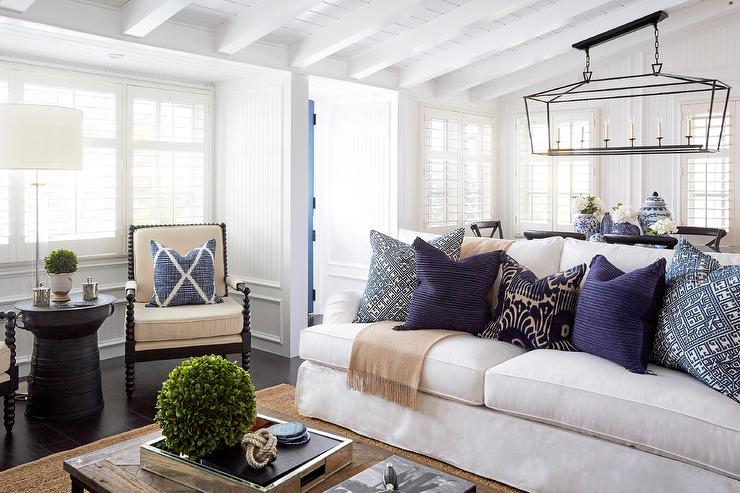Beautiful Living Room Features A White Sofa Lined With Blue And Purple  Pillows Facing A Salvaged Wood Coffee Table Placed Atop A Jute Rug.
