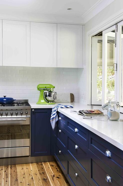Beautifully Appointed Blue And White Kitchen Boasts Navy Cabinets Fitted With Polished Nickel Hardware A Quartz Countertop Positioned Beneath