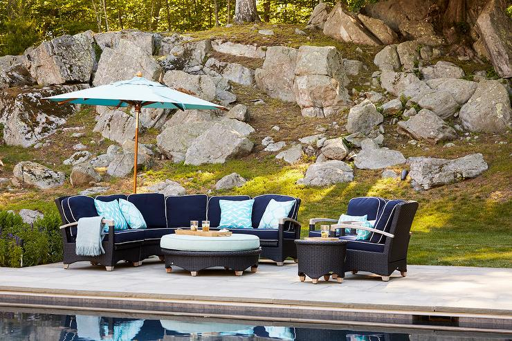 In Front Of An In Ground Pool, Around Turquoise Ottoman Seats Two Navy Blue  Accent Chairs Beside A Woven End Table And A Blue Sectional Topped With ...