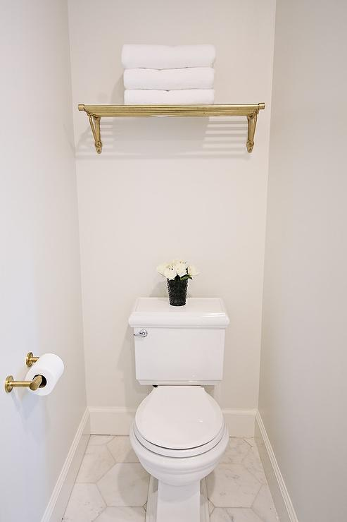 A brass towel rack is mounted to a white wall above a toilet fixed to  marble hexagon floor tiles beside wall mounted brass toilet paper holder. Brass Towel Rack Over Toilet Design Ideas