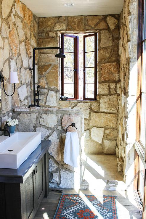 rustic stone shower with tumbled marble brick floor