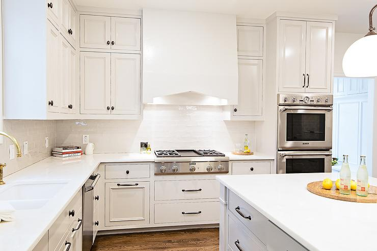 White glazed kitchen tiles with brass swing arm pot filler for White kitchen cabinets with oil rubbed bronze hardware