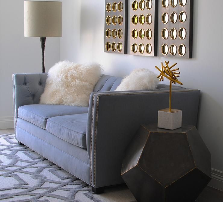 Chic Living Room Features A Blue Tufted Velvet Sofa Placed On A Global  Views Arabesque Rug And Topped With White Sheepskin Pillows Positioned  Beneath Wall ...