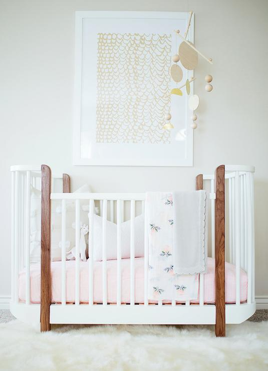 Marvelous Chic Girlu0027s Nursery Features A Gold Art Piece Placed Over An Oval Two Tone  Crib Dressed In Pink Bedding Adorned With An Unique Mobile.