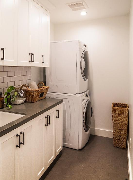 white laundry room features white cabinets adorned with bronze pulls paired with a black quartz countertop and a white subway tiled backsplash finished with