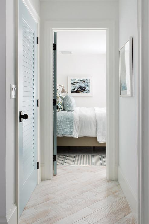 White Washed Wood Floors Lead Past A Blue Louvered Closet Door To A Bedroom  Fitted With A White And Blue Striped Rug Placed Beside A Tan Upholstered  Bed ...