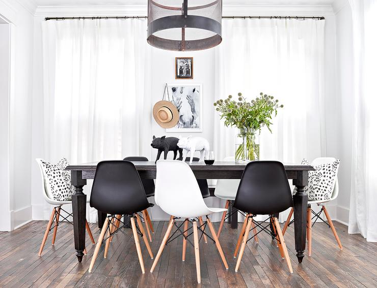 dining table lined with a mix of black and white dining chairs eames