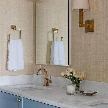 blue bath vanity cabinets topped with a carrera marble countertop