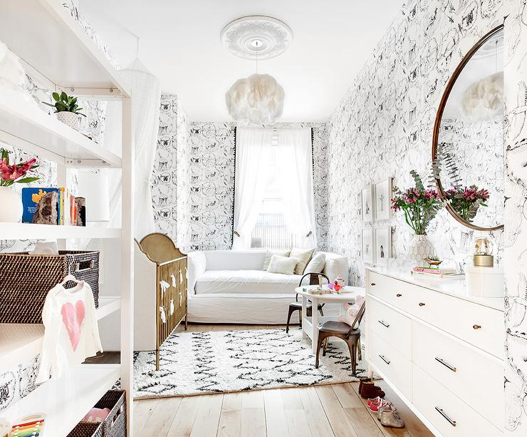 Whimsical Nursery Is Clad In Kalahari Vignettes Wallpaper Illuminated By A White Feather Chandelier Hung Over Black And Moroccan Rug Placed Beneath