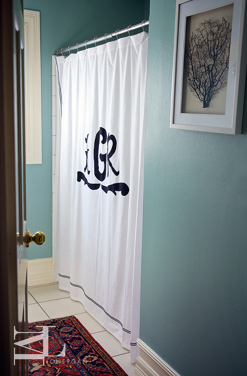 blue bathroom with black and white monogrammed shower curtain