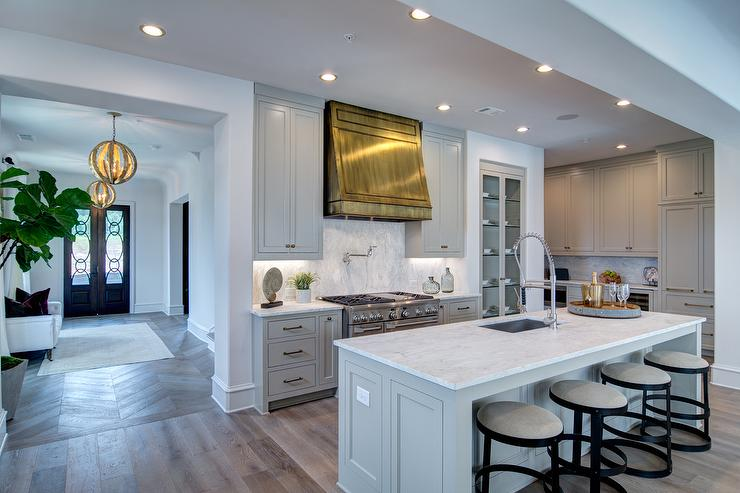Light Gray Kitchen Cabinets With Polished Brass Range Vent
