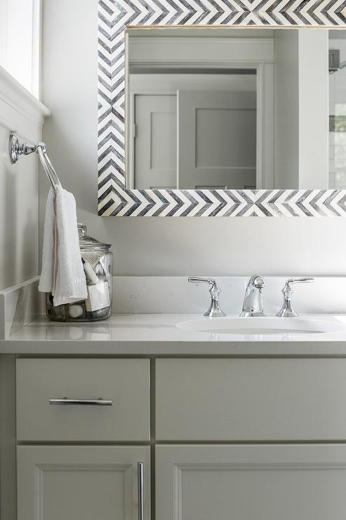 Exquisite gray and white bathroom features a gray bath vanity fitted with  polished nickel pulls and a white quartz countertop finished with an oval  sink. White Vanity Gray Quartz Countertop Design Ideas