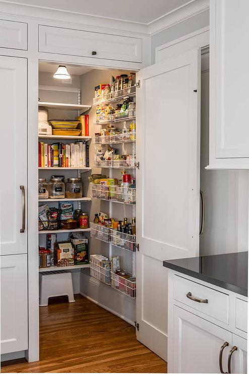 Amazing A White Paneled Cabinet Doors Opens To Reveal A Hidden Kitchen Pantry  Equipped With Stacked White Metal Spice Baskets Mounted On A Gray Wall  Adjacent To ... Part 25