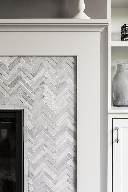 Gorgeous fireplace is fitted with a white fireplace mantle framing gray herringbone marble surround tiles.