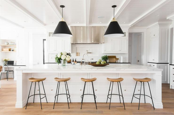 large kitchen island. Five sleek wood and island counter stools sit in front of a large white  fitted with stacked drawers donning polished nickel knobs marble White Island Black Light Pendants Transitional Kitchen