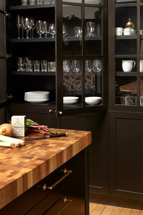 Chic Black Kitchen Features Black China Cabinets Fitted With Glass Front  Doors Adorned With Brass Knobs Facing A Black Center Island Topped With  Thick ...