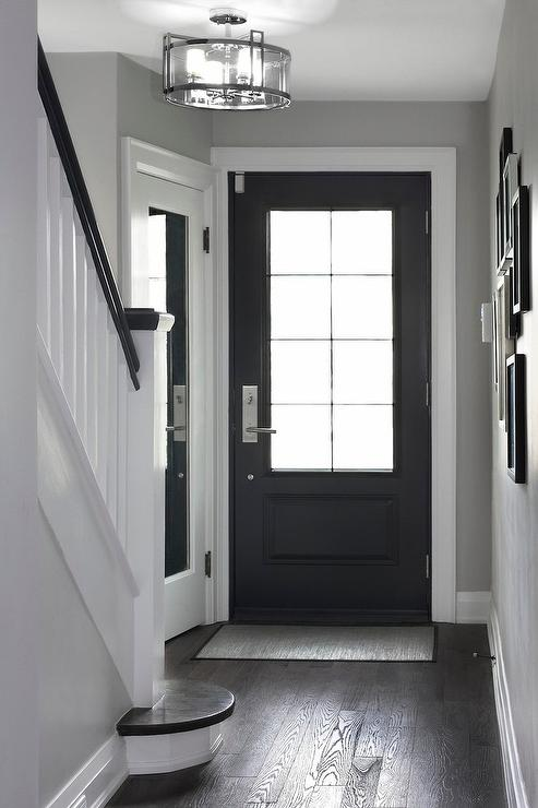 A Black Front Door With 8 Glass Panes Opens To A Chic Foyer Filled With A  Corner Coat Closet Accented With A Full Length Mirror Illuminated By A  Glass Semi ...