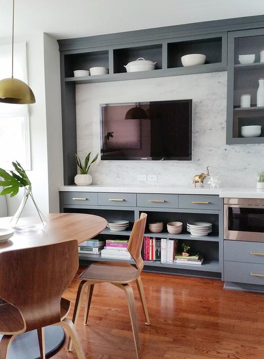 Watch TV While You Eat In A Contemporary Dining Room Featuring Flat Paneled Television Mounted To Marble Backsplash Positioned Beneath Overhead Display