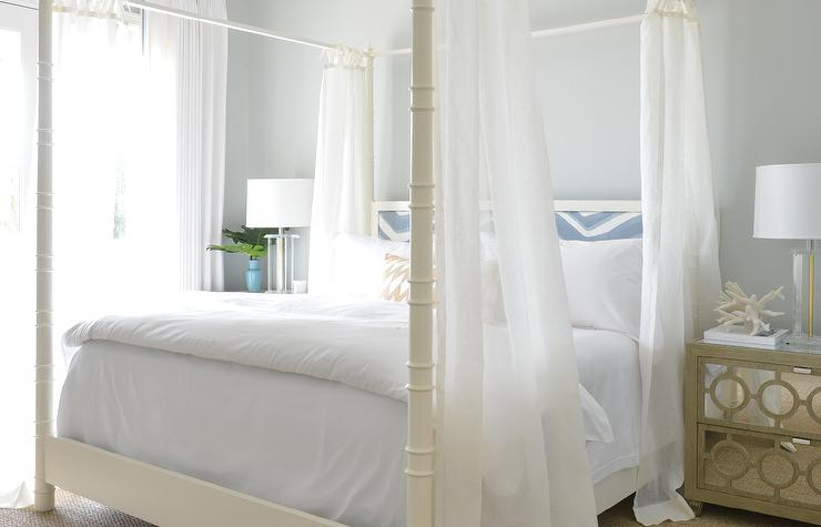 restful white bedroom boasts a white faux bamboo canopy bed accented with a blue chevron headboard white hotel bedding and sheer bed panels - Light Hardwood Canopy 2016