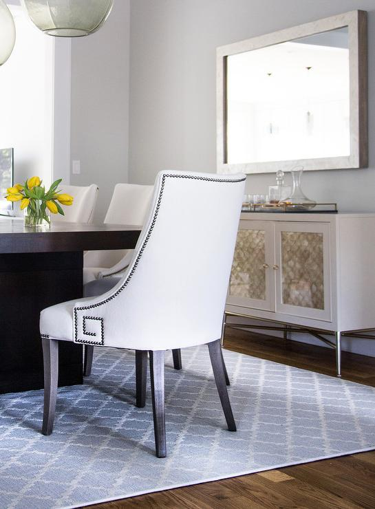 centered on a blue trellis rug an espresso stained dining table is surrounded by white dining chairs accented with a nailhead greek key trim as a bernhardt