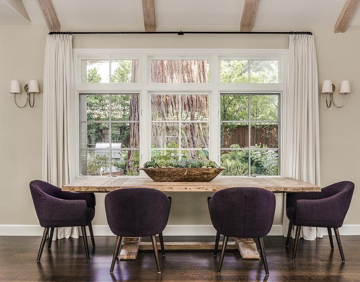 Chic Dining Room Boasts A Salvaged Wood Table Pushed Against Wall With Windows Dressed In White Curtains Lined Purple Linen Chairs
