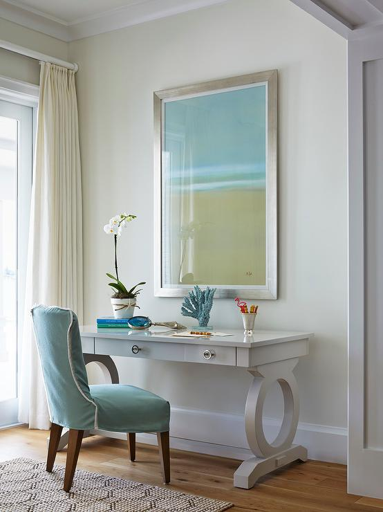 Master Bedroom Boasts A Wall Painted Pale Yellow Lined With Green And Blue Abstract Art Piece Placed Over Gray Desk Paired Slipcovered Chair