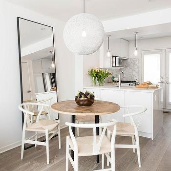 Round Wood Top Dining Table with White Wishbone Chairs. Black Leaning Dining Room Mirror Design Ideas