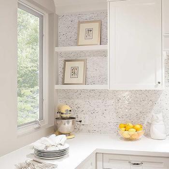 backsplash tiles beside white floating shelves located adjacent to a