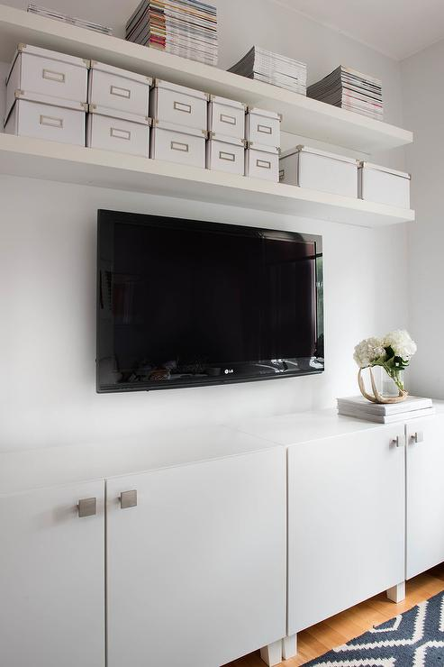 Perfectly organized living room features white floating shelves mounted  above a television fixed over white flat front TV cabinets.