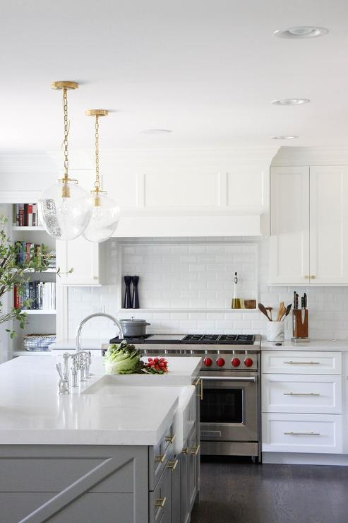 white and gray kitchen boasts a dual wolf range positioned between white shaker cabinets adorning nickel pulls and a white quartz countertop - Acorn Kitchen Cabinets