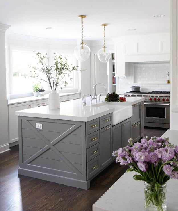 beautifully designed gray shiplap center island is accented with brass cabinet pulls and a farmhouse sink with a polished nickel deck mount gooseneck faucet. beautiful ideas. Home Design Ideas