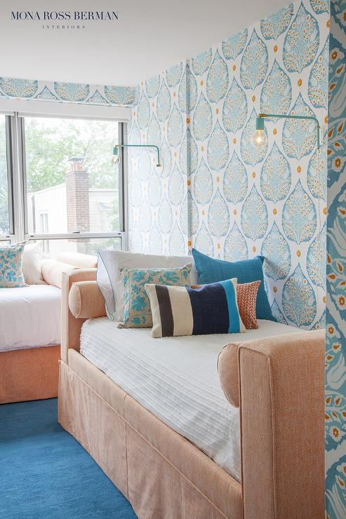 peach colored daybeds dressed in colorful pillows illuminated by teal