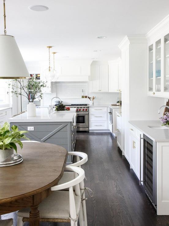 u shaped white and gray kitchen boasts dark stained oak floor complementing a gray shiplap island topped with a white quartz countertop finished with an - Acorn Kitchen Cabinets