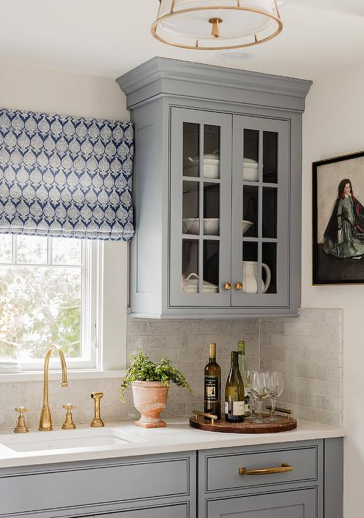 A blue gray glass front cabinet adorning antique brass knobs is mounted  beside a window dressed in a white and blue roman shade positioned above an  antique ... - Antique Brass Kitchen Cabinet Hardware Design Ideas