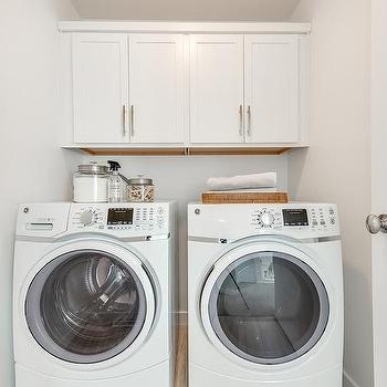 White Laundry Room With Cabinets Over Washer And Dryer