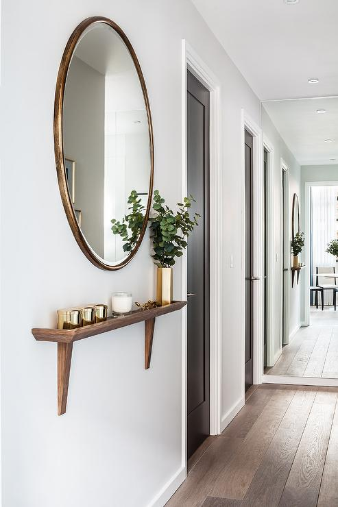 Chic Foyer Hallway Features A Round Gold Oversized Mirror Placed Over Walnut Stained Wood Wall Shelf With Brackets