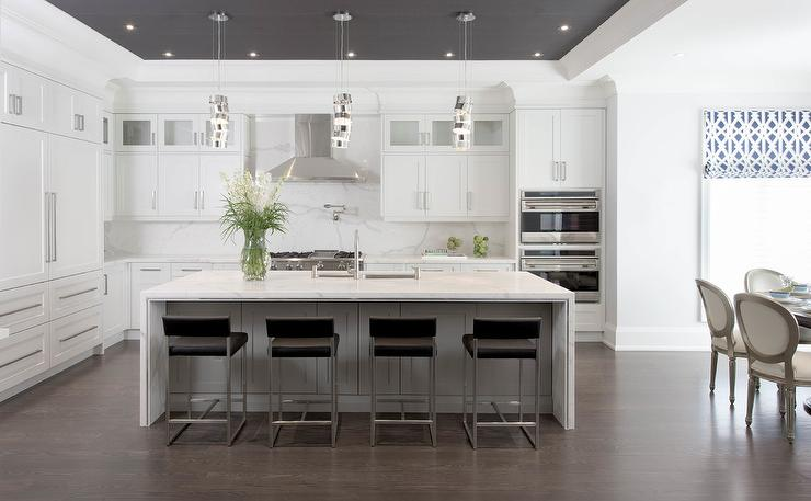 Large White L Shaped Kitchen Is Fitted With Black Modern Counter Stools  Positioned On Brushed Oak Engineered Wood Floors In Front Of A White Kitchen  Island ...